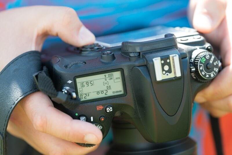 Kursteilnehmer prüft Einstellungen seiner Kamera